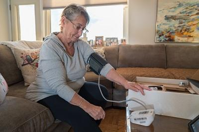 Older gray-haired woman taking blood pressure with cuff attached to monitoring device