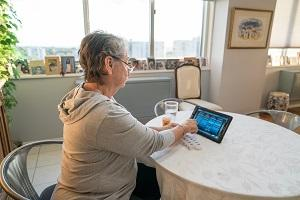 Gray-haired woman seated at table with daily medication container and digital tablet